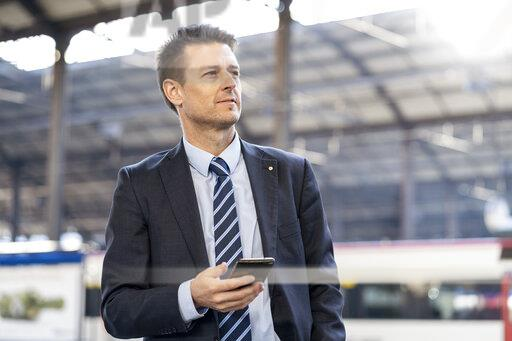Businessman with cell phone at train station