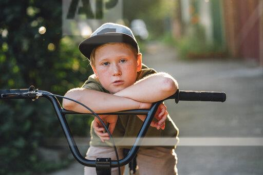 Portrait of boy with bmx bike on road