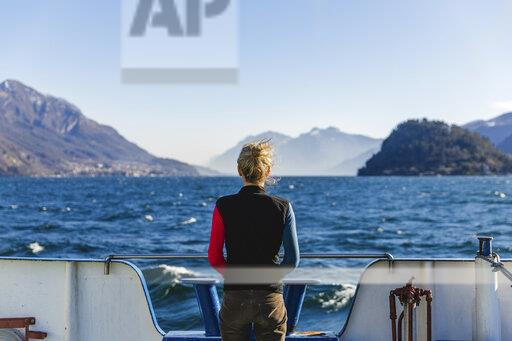 Italy, Como, rear view of woman on the ferry enjoying the view of Lake Como
