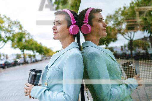Woman dressed in jacket with thermo mug and pink headphones, reflection