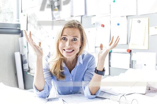 Portrait of stressed woman sitting at desk in office surrounded by paperwork