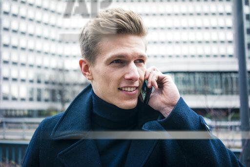 Portrait of smiling young man talking on cell phone in the city