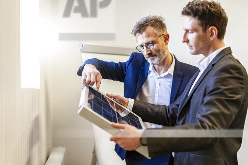 Two businessmen in office with solar cell discussing