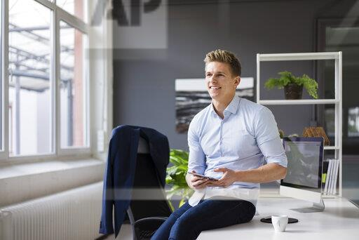 Smiling young businessman sitting on desk in office holding tablet