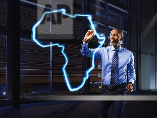 Businessman painting Africa with light