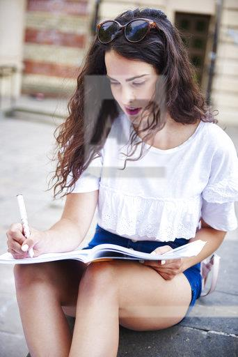 Porrtait of young woman sitting outdoors writing in notebook