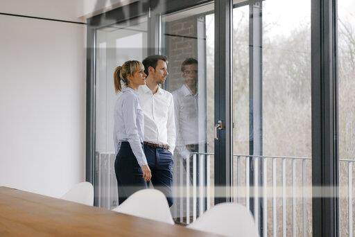 Successful businesswoman and businessman in conference room, looking out of window