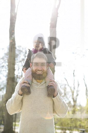Portrait of happy father carrying daughter on shoulders in park