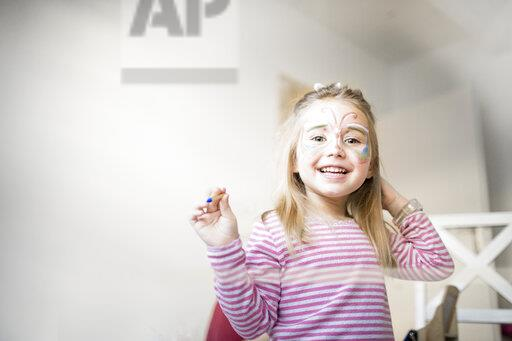 Portrait of smiling little girl made up as butterfly