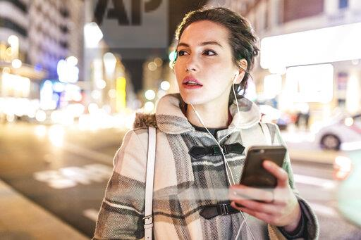 Spain, Madrid, young woman in the city at night using her smartphone and wearing earphones