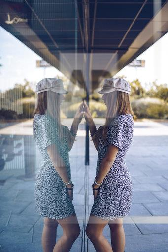 Attractive young woman in leopard print dress reflected in windowpane