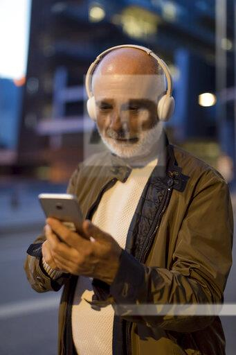 Spain, Barcelona, senior man with headphones and cell phone in the city at dusk
