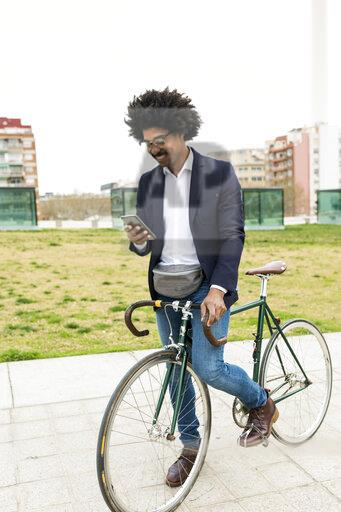 Spain, Barcelona, smiling businessman on bicycle using cell phone in the city