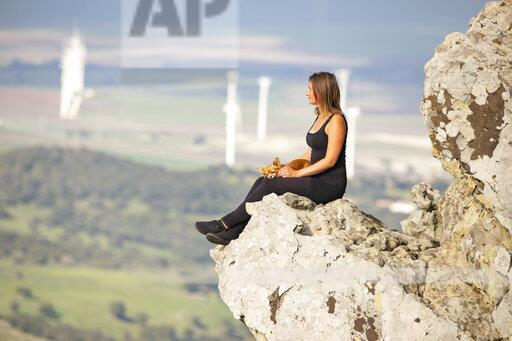 Young woman with lap dog sitting on rock, looking at distance