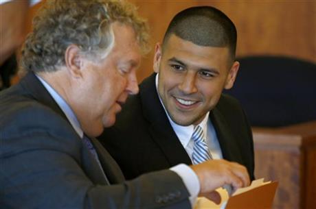 Former NFL player Aaron Hernandez (R) smiles at his lawyer, Michael Fee, during a hearing in Bristol County Superior Court in Fall River