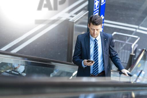 Businessman with suitcase and cell phone on escalator