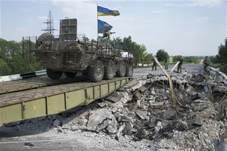 An Ukrainian government army' vehicle travels across a damaged bridge near the village of Debaltseve, Donetsk region, eastern Ukraine, Thursday, July 31, 2014. (AP Photo/Dmitry Lovetsky)