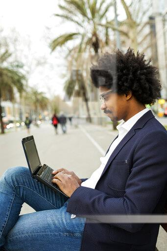 Spain, Barcelona, businessman in the city sitting on bench using laptop