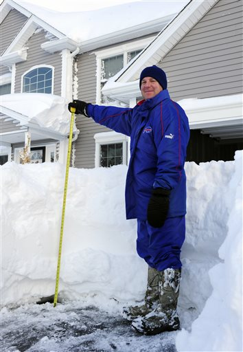 Art Hauret pauses after he measures the nearly four foot accumulation of snow in his driveway on Summerfield Drive in Lancaster, N.Y. Wednesday, Nov. 19, 2014.