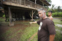 In this Wednesday, Sept. 12, 2018 photo, Honokohau Valley resident Mundy Gillcoat describes to his son how high flood waters raged outside their home in Maui, Hawaii. Honolulu officials are asking residents near a dam to stay alert for the possibility of evacuating as water levels in the reservoir rise amid heavy rains. Tropical Storm Olivia dumped heavy rains on Maui and Oahu as it crossed the state. (Chris Sugidono/The News via AP)