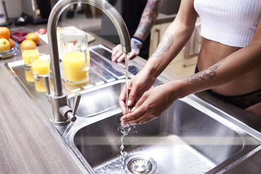 Close-up of tattooed woman washing hands in kitchen