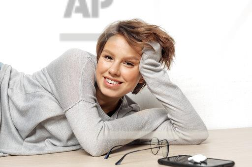 Portrait of smiling young woman lying on the floor