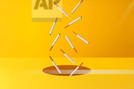 Cigarettes falling into a hole in yellow background