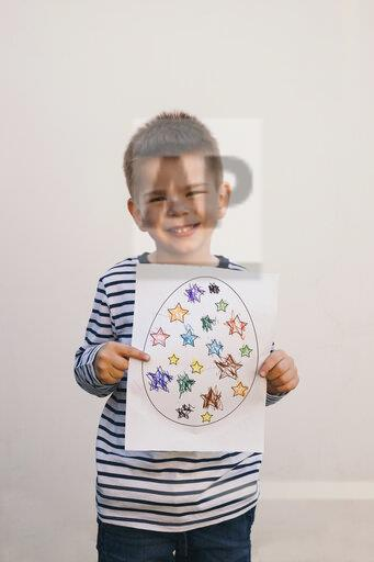 Boy holding his art work and smiling
