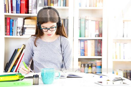 Girl listening music with headphones while doing homeworks