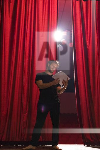 Barefoot actor standing on stage of theatre reading script