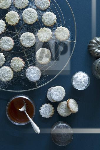 Christmas Cookies Spitzbuben on a baking grid, jam in a jar, Rosehip Jam, icing sugar