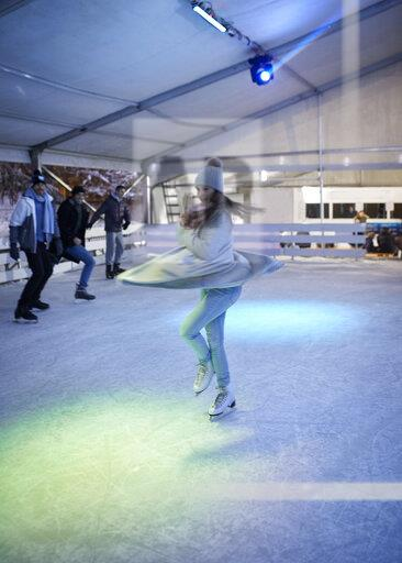 Young woman doing a pirouette on an ice rink at night watched by her friends