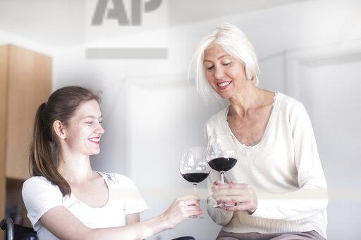 Mother and daughter in the wheelchair with a glass of red wine at home
