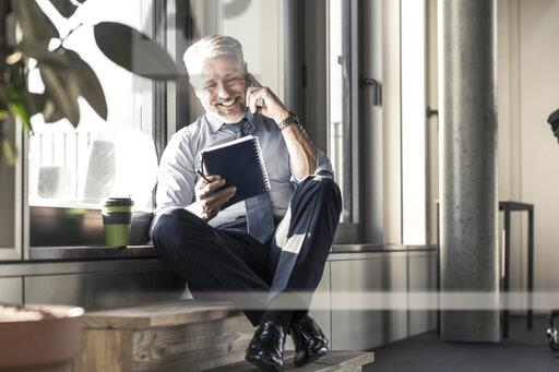 Smiling mature businessman with notebook sitting at the window talking on cell phone