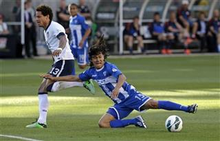 Roger Espinoza (15) falls as Jermaine Jones