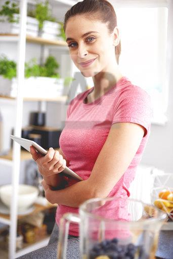 Portrait of smiling young woman with tablet in the kitchen
