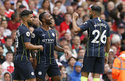 Manchester City's Raheem Sterling, center, celebrates with Sergio Aguero and Riyad Mahrez, right, after scoring the opening goal during the English Premier League soccer match between Arsenal and Manchester City at the Emirates stadium in London, England, Sunday, Aug. 12, 2018. (AP Photo/Tim Ireland)