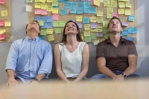 Smiling colleagues sitting in front of wall with sticky notes in office looking up