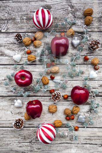 Christmas apples, walnuts, hazelnuts and Christmas decoration on wood