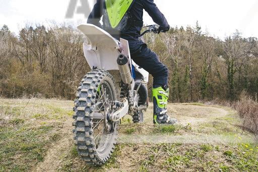 Close-up of motocross driver standing on circuit