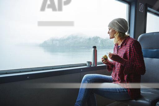 Chile, Hornopiren, woman looking out of window of a ferry eating an avocado