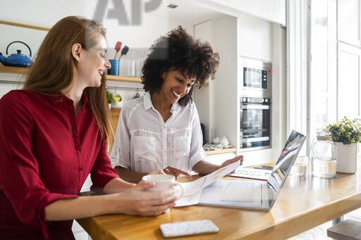 Two women working together in kitchen, using laptop, discussing documents