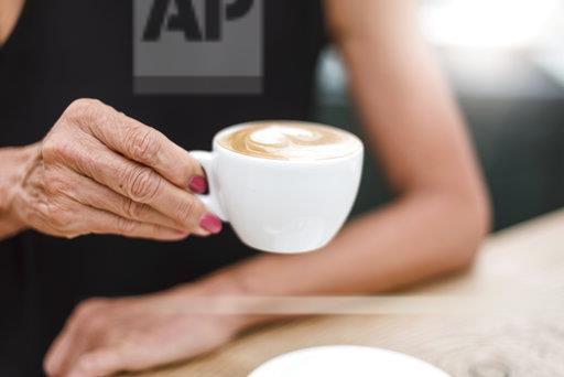 Close-up of senior woman holding a cup of cappuccino