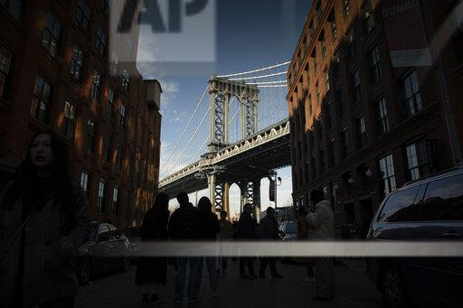 Tourists taking pictures of the Manhattan bridge seen from Dumbo, Brooklyn