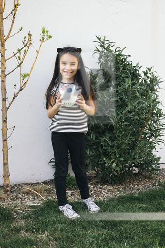 Girl holding painted Easter egg in garden