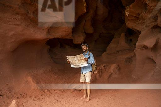 Young man standing in a cave, looking at map