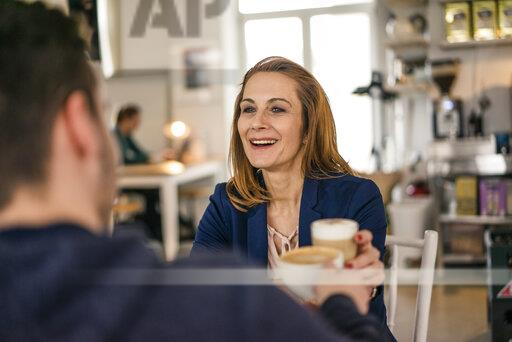 Businesswoman sitting in a cafe, drinking coffee with a colleague