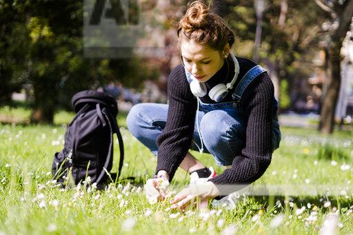 Young woman picking daisies in a park