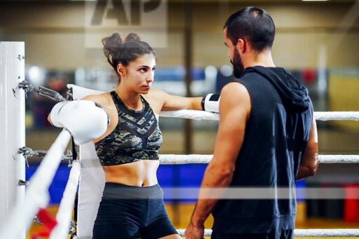 Trainer giving instructions in the corner to a female boxer before the fight