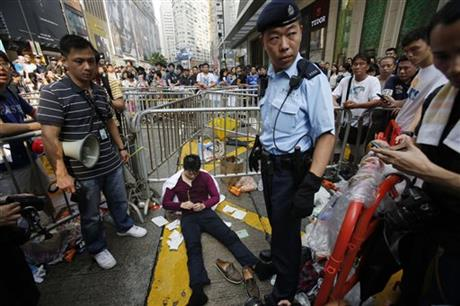 A police guards over a pro-democracy student protester who collapsed during scuffles with locals trying to remove the barricades blocking local streets in Causeway Bay, Hong Kong, Friday, Oct. 3, 2014. Hong Kong protest leaders on Friday welcomed an offer by the territory's leader of talks to defuse the crisis over demonstrations seeking democratic reforms, though they continued to demand he resign and maintained barricades around government headquarters, frustrating staff going to work.